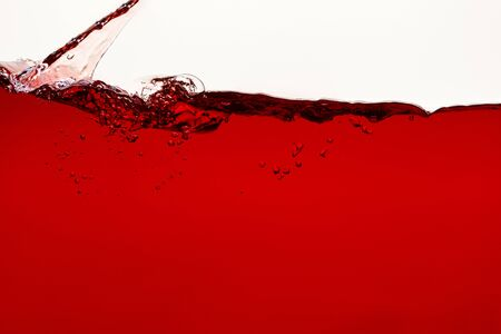 flowing red liquid with splash and bubbles isolated on white