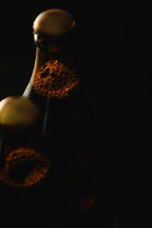 close up view of glass bottles of beer with bubbles isolated on black