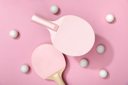 top view of white table tennis balls and rackets on pink background