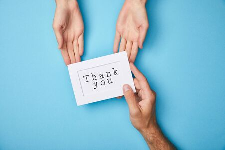 cropped view of man giving white card in frame with thank you lettering to woman on blue background