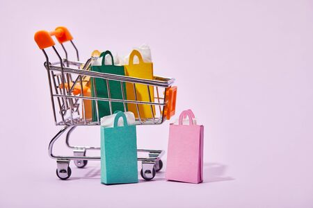 toy cart with colorful paper bags near few shopping bags on violet background