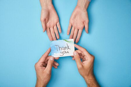 cropped view of man giving greeting card with thank you lettering to woman on blue background