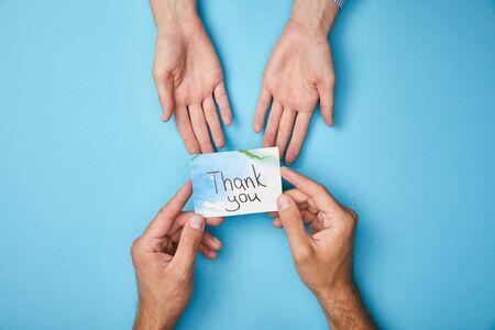 Vista recortada del hombre dando tarjeta de felicitación con letras de agradecimiento a la mujer sobre fondo azul.