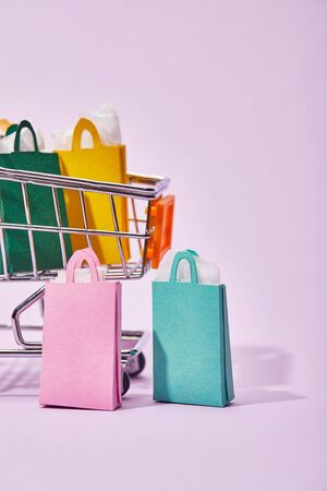 few shopping bags near toy cart with colorful paper bags on violet background