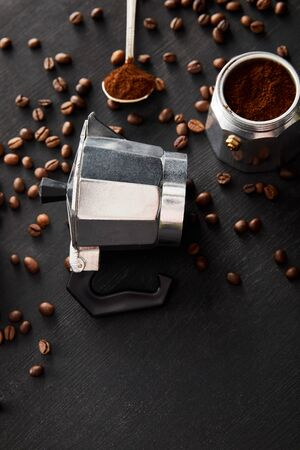 Separated parts of geyser coffee maker near spoon on dark wooden surface with coffee beans