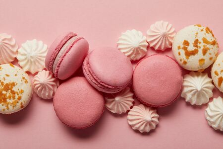 Pink and white tasty macaroons with pink and white meringues on pink background