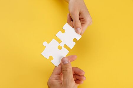 cropped view of woman and man matching pieces of white puzzle on yellow background Banco de Imagens - 130574822