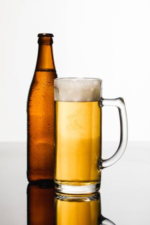 glass of beer with foam near wet bottle isolated on white