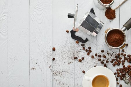 Top view of geyser coffee maker near portafilter, spoon and cup of coffee on white wooden surface with coffee beans