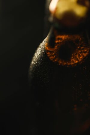 close up view of wet bottle of beer with bubbles isolated on black Stock Photo