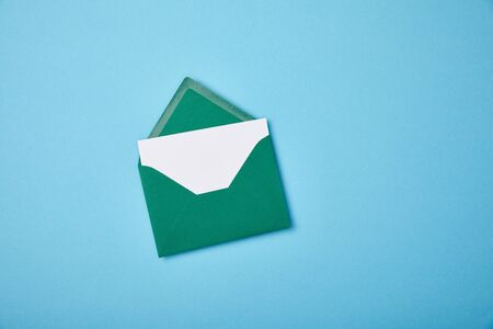 green envelope with blank white card on blue background