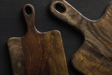 Top view of brown wooden cutting boards on dark surface