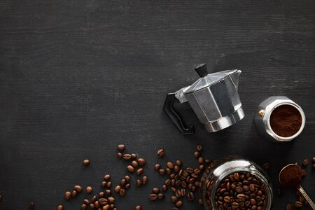 Top view of parts of geyser coffee maker near spoon and glass jar on dark wooden surface with coffee beans