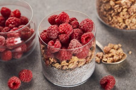 selective focus of tasty yogurt with raspberries, oat flakes and chia seeds near teaspoon on marble surface