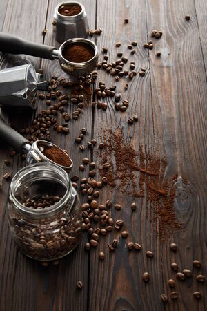 Dark wooden surface with glass jar, portafilters, geyser coffee maker and coffee beans