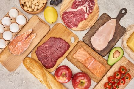 Top view af raw organic assorted meat, poultry, fish, eggs, apples, lemon, avocado, tomatoes and peanuts on wooden cupboards with fresh baguette on marble surface Banco de Imagens