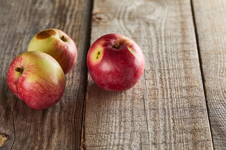 apples with small rotten spot on wooden surface 免版税图像