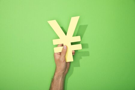 cropped view of man holding yellow yen currency sign on green 写真素材