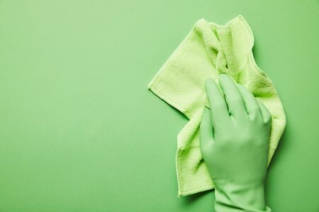 cropped view of man in rubber glove holding green rag