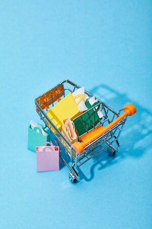 toy cart with colorful paper bags near few shopping bags on blue background