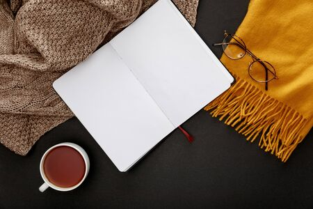 top view of tea in mug near warn scarves and blank notebook on black background