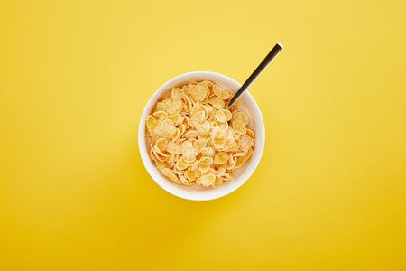 top view of bowl with cornflakes isolated on yellow Stock Photo