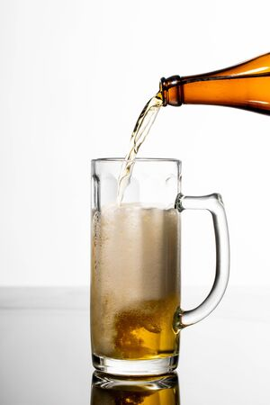 beer pouring from bottle into glass on table isolated on white