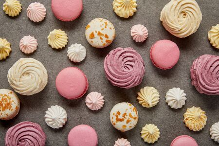 Top view of assorted pink white and yellow macaroons with meringues on gray background