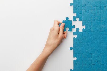 Ausgeschnittene Ansicht einer Frau, die blaues Puzzle auf weißem Hintergrund anbringt