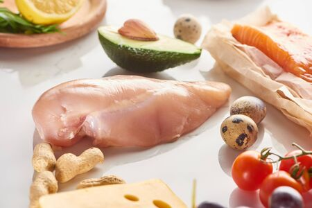 Close up view of raw poultry and salmon fillet near quail eggs, peanuts, tomatoes, avocado, lemon and cheese on white surface