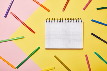top view of blank notebook with multicolored felt pens on pink and yellow background Stock fotó