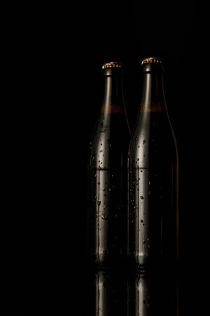 glass bottles of beer with drops isolated on black Stock Photo