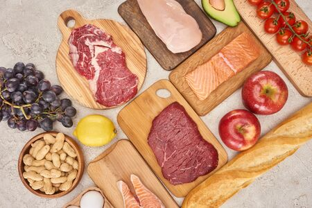 Top view af raw organic assorted meat, poultry, fish, apples, grape, lemon, avocado, tomatoes and peanuts on wooden cupboards with fresh baguette on marble surface
