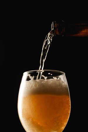 beer flowing from bottle into glass isolated on black Stock Photo - 130574626