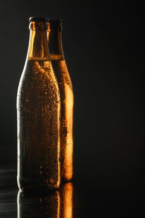 glass bottles of beer with drops isolated on black Imagens