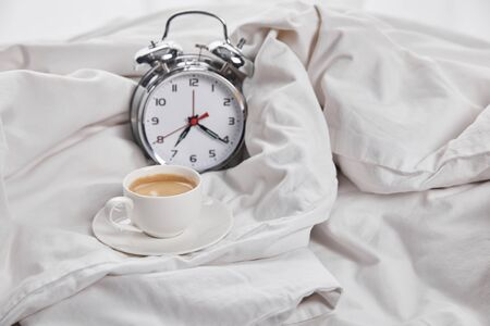 coffee in white cup on saucer near silver alarm clock in white bed