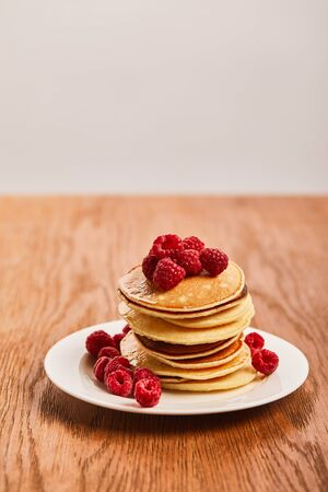 selective focus of pancakes with raspberries on plate on wooden surface isolated on grey