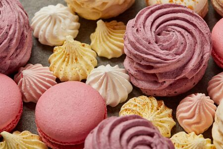 Pink zephyr with small yellow and pink meringues and pink macaroons on gray background