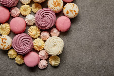 Top view of assorted delicious french macaroons with meringues on gray background 写真素材