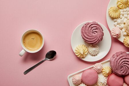 Top view of pink, white and yellow meringues, macaroons, marshmallows and cup of coffee with spoon on pink background