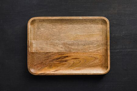 Top view of brown wooden empty dish on dark surface Stock fotó