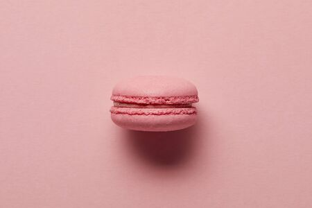 Pink french macaroon in center on pink background