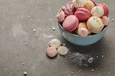 Delicious french macaroons and meringues in blue bowl and smashed sugar pieces on gray background 写真素材