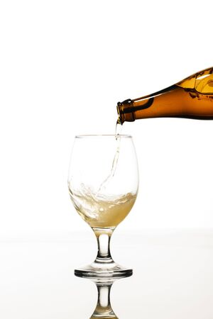 beer pouring from bottle into glass isolated on white Stock Photo
