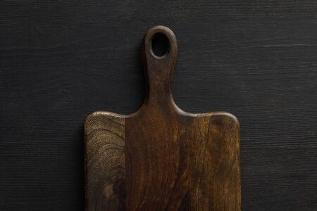 Top view of brown wooden cutting board on dark surface