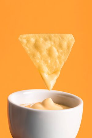 crispy corn nacho with cheese sauce in bowl isolated on orange, Mexican cuisine