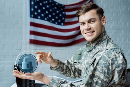 happy military man gesturing in office near virtual padlock and laptop