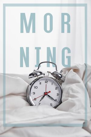 silver alarm clock in blanket in white bed with morning illustration Stok Fotoğraf