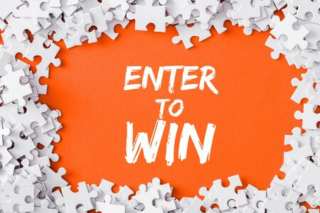 top view of frame of white jigsaw puzzle pieces around of enter to win lettering on orange Stok Fotoğraf - 130884808