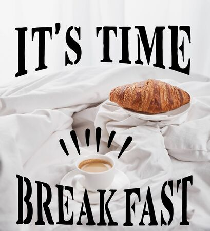 fresh croissant on plate near coffee in white cup on saucer in bed with its time, breakfast lettering Stock fotó